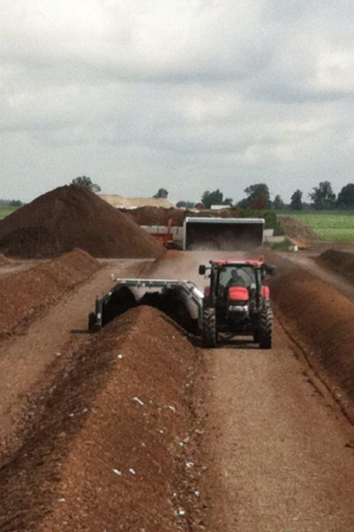 Turning a windrow of compost.